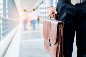 businessman holding a briefcase travellers walking outdoors