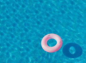 Vue aérienne d'une piscine avec une bouée rose qui flotte