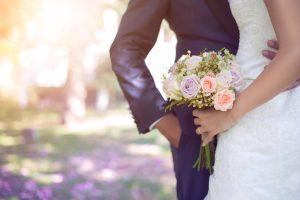 Deux mariés côte à côte. L'homme tient la femme. La mariée tient un bouquet de fleurs.