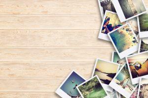 Plusieurs photographies diverses posées sur une table en bois