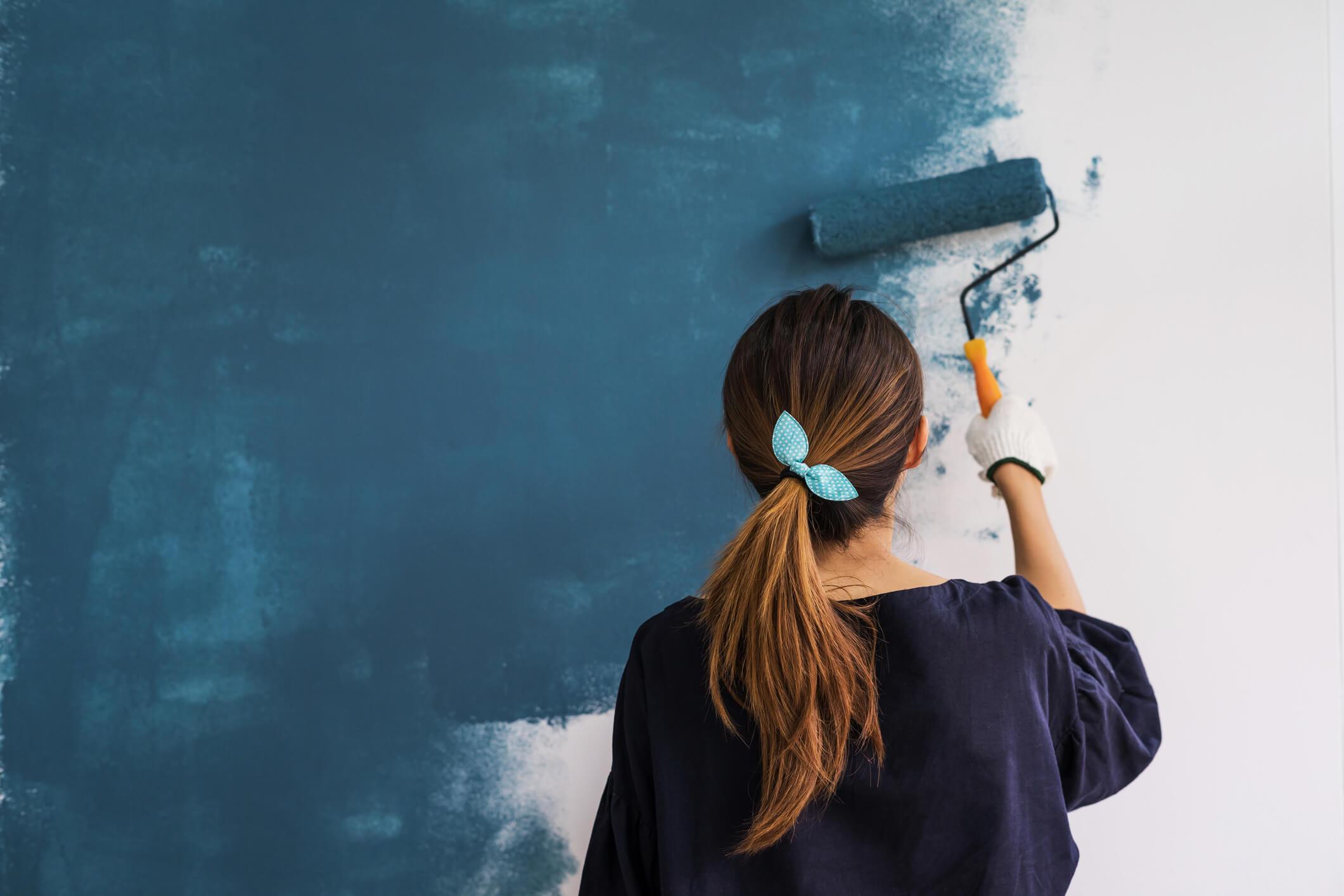 Une femme de dos fait de la peinture chez elle