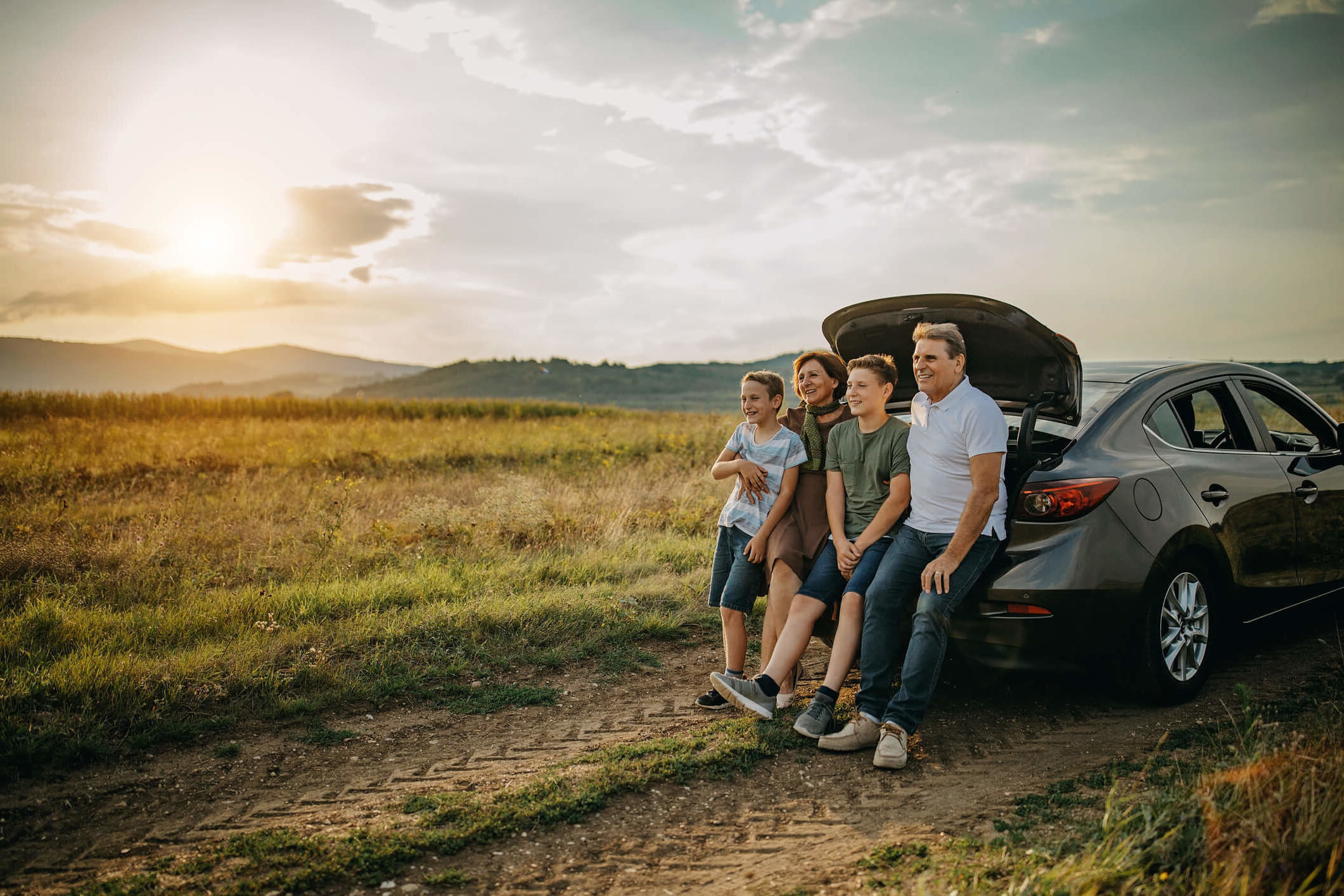 Family of four (a mother, father and two boys) leaning against a car looking over a field